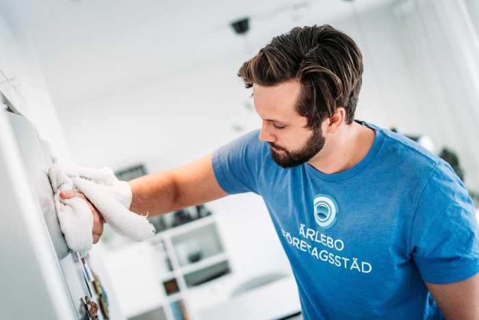 Tobias Ärlebo kollar mot ett kylskåp i ett kök och rengör kylen med en vit trasa