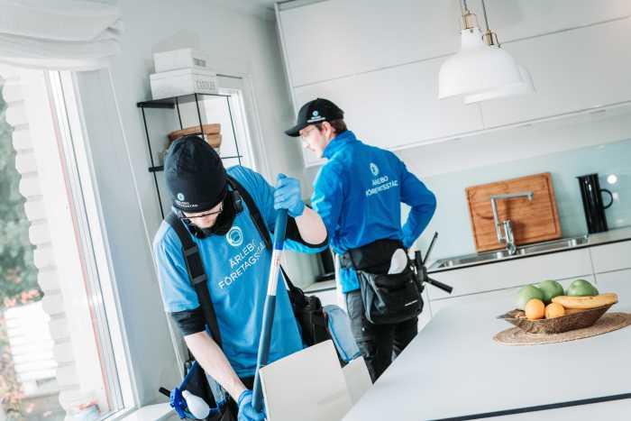 Två städare från Ärlebo Företagsstäd i ett kök, en person putsarfönster och en rengör golvet