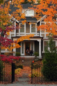 A couple sit on their front porch enjoying the colors and warm weather of an autumn evening.