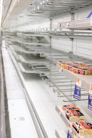 Once filled with varieties of cheese, yogurt, juice, eggs, butter, and various other items, the back wall case at Johnnies Foodmaster stands mostly empty, save for some last few items that are being sold at a discount. November 9, 2012.