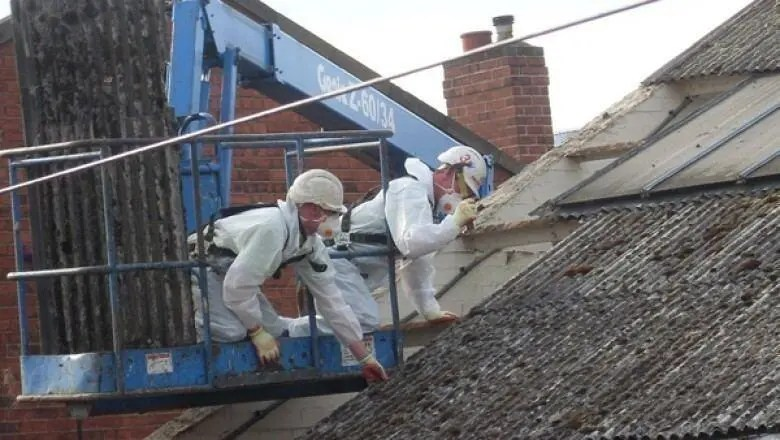 Asbestos removal operatives removing asbestos cement roof sheets