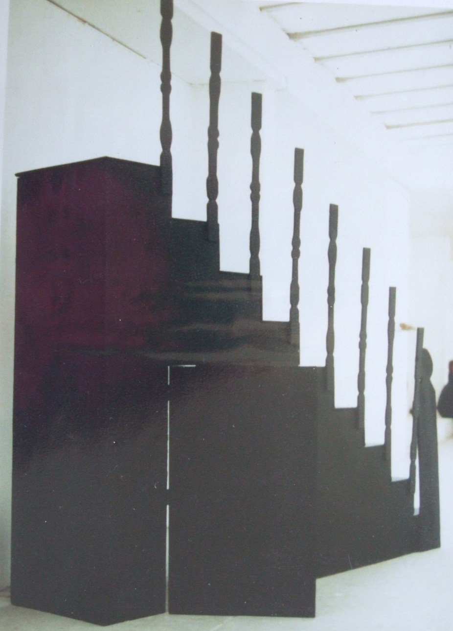 Lifesize model of staircase, painted black, with an opening to the rear.