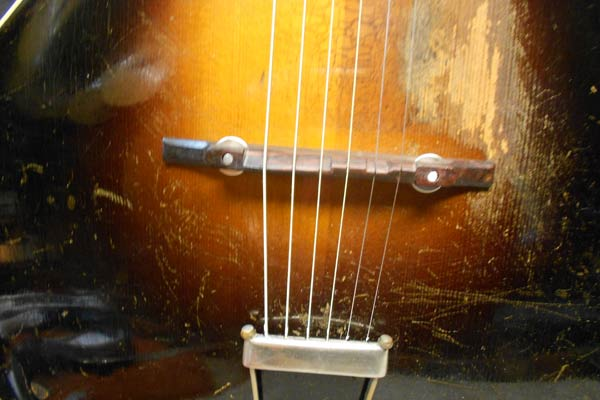 Arnie Gamble makes new bridges for old Gibson arch top guitars.