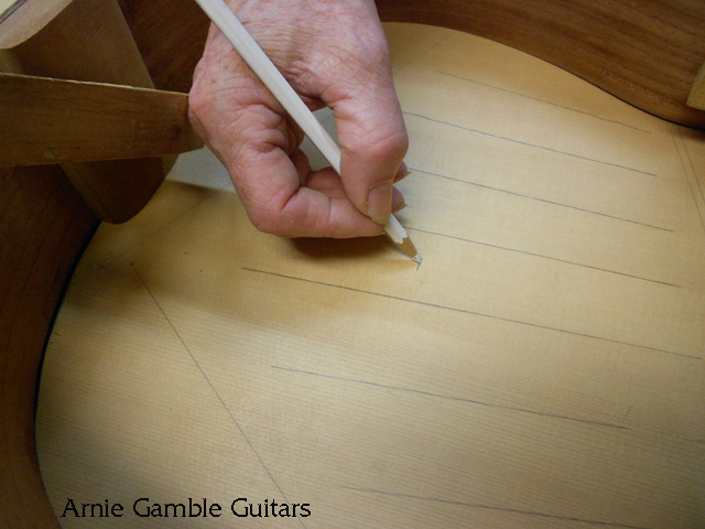Marking the bridge location on the inside of the top of the guitar.