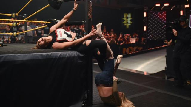 Charlotte Flair twists Rhea Ripley's legs aroud the post and hangs off them