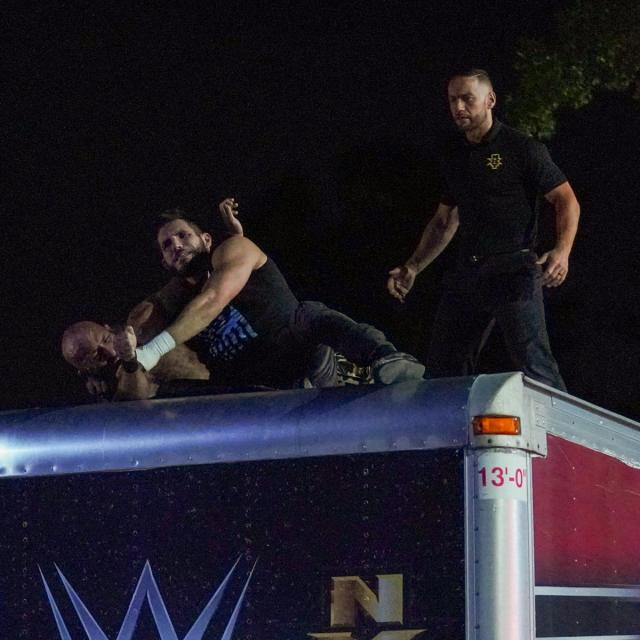Johnny Gargano and TOmmaso Ciampa fight on top of a truck while the ref watches on