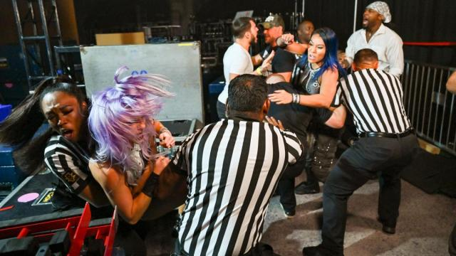 Johnny Gargano and Isaiah 'Swerve' Scott argue while officials try to separate Mia Yim and Candice LeRae