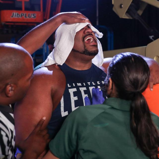 Keith Lee is tended to by medics after Karrion Kross and Scarlett's fireball attack