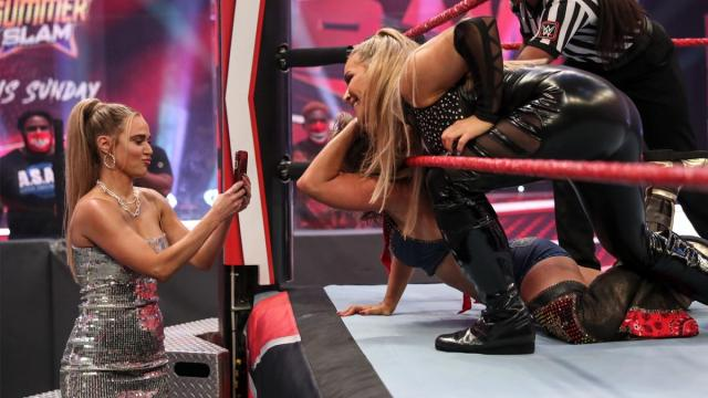 Natalya poses for Lana with Mickie James trapped in the corner