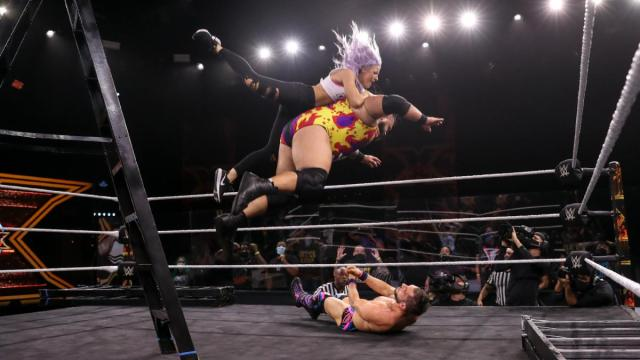 Bronson Reed splashes Johnny Gargano with Candice LeRae on his back