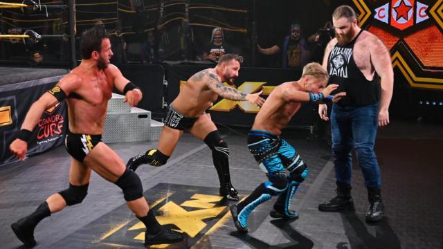 Roderick Strong and Bobby Fish throw Drake Maverick at Killian Dain, who watches him go past