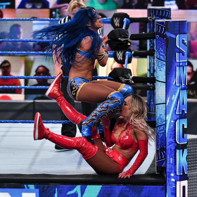 Sasha Banks delivers double knoees to Carmella against the ringpost.
