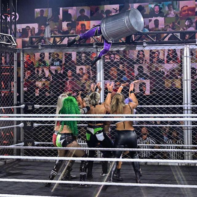 Io Shirai enters the WarGames match from the top of the cage, inside a trashcan, into everyone else