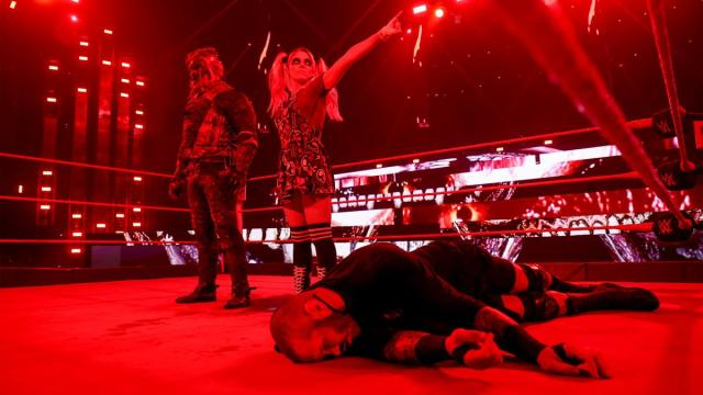 Alexa Bliss stands by the side of The Fiend and points at the WrestleMania sign, with Randy Orton laid out in front of them