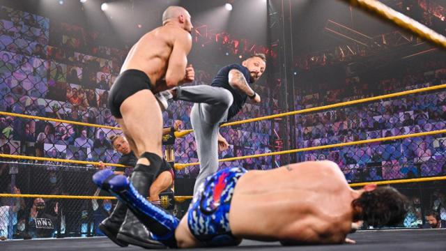 Bobby Fish kicks Oney Lorcan in the stomach with Kyle O''Reilly laying in the foreground.