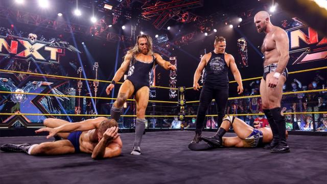 Pete Dunne, Ridge Holland, and Oney Lorcan stand over Timothy Thatcher and Tommaso Ciampa