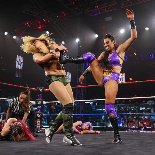Indi Hartwell kicks Zoey Stark in the head, with Candice LeRae and Io Shirai laid out in the background
