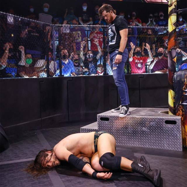 Kyle O'Reilly stands over Adam Cole after giving him a brainbuster on the steps