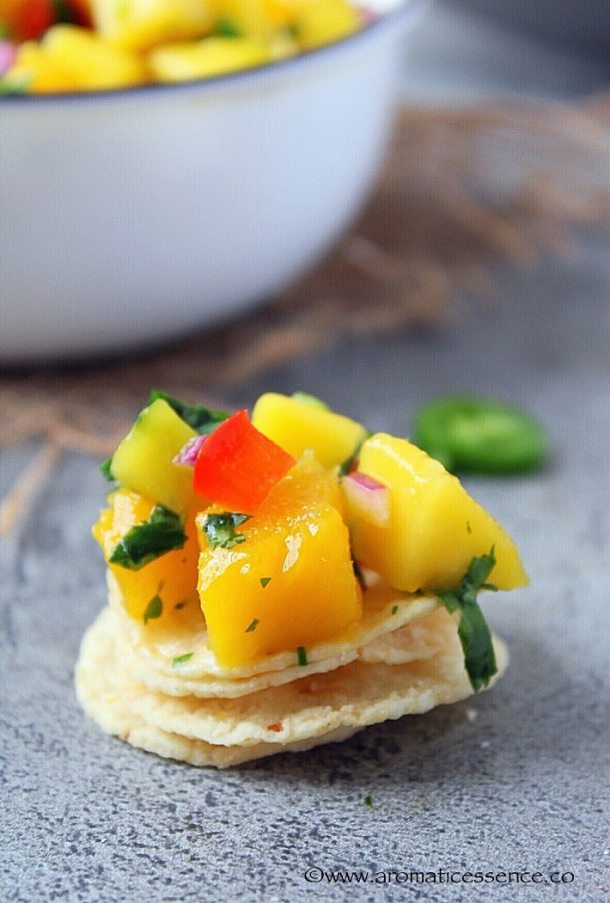 Mango salsa on top of a stack of tortilla chips.