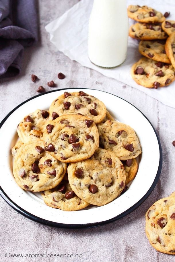 Egg-free chocolate chip cookies in a white rimmed plate with some cookies in the background along with a bottle of milk.
