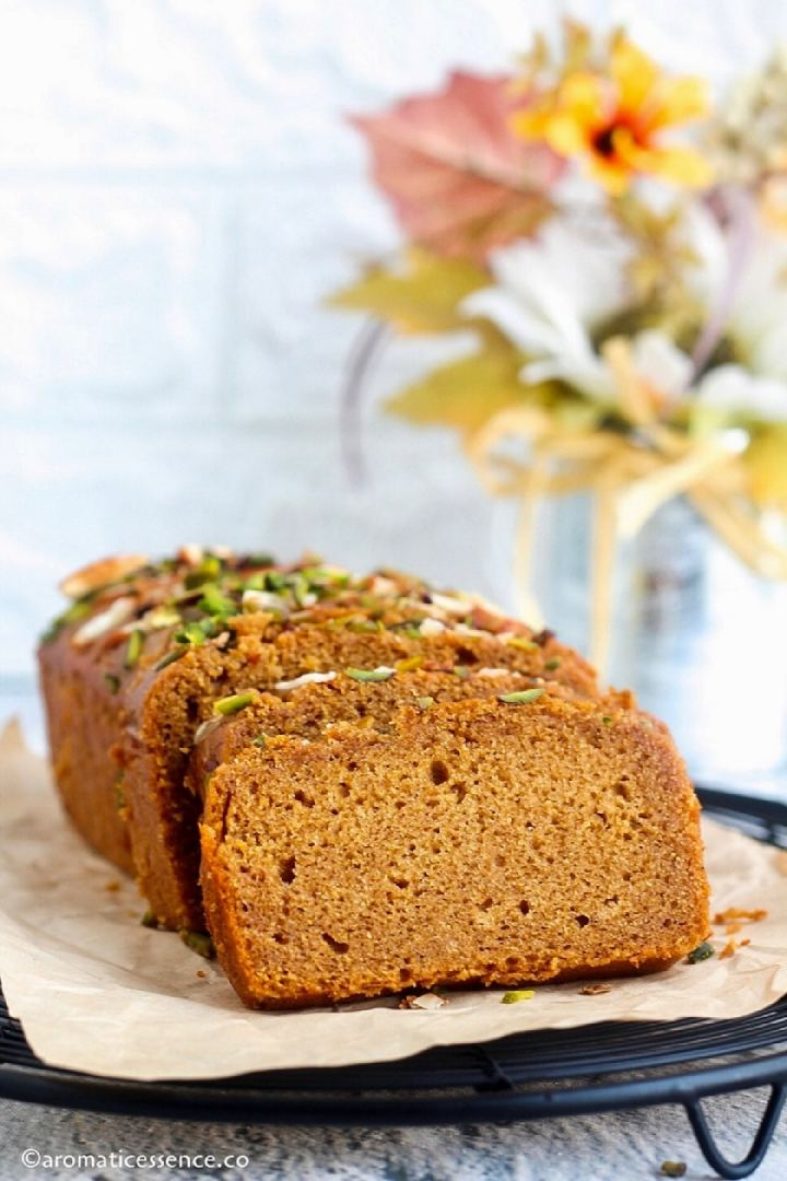 Eggless wheat loaf cake on a round wire rack, with a pot of flowers in the background