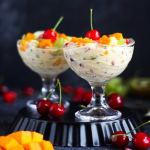 fruit cream topped with cherries, mangoes, grapes, and pomegranate arils