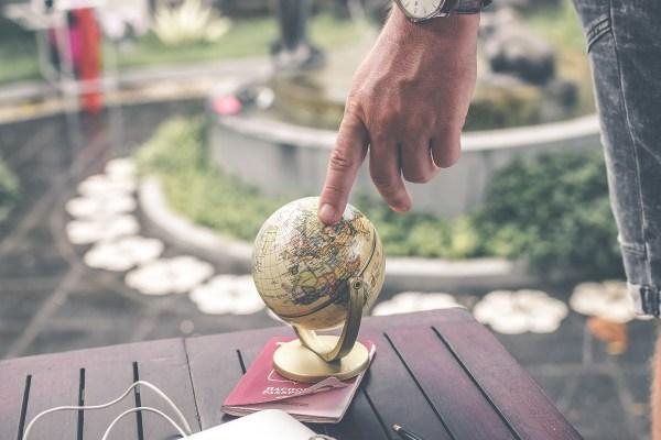 男性アロマセラピストがグローバルスタンダードであることを示す画像。地球儀を指す男性アロマセラピストの画像