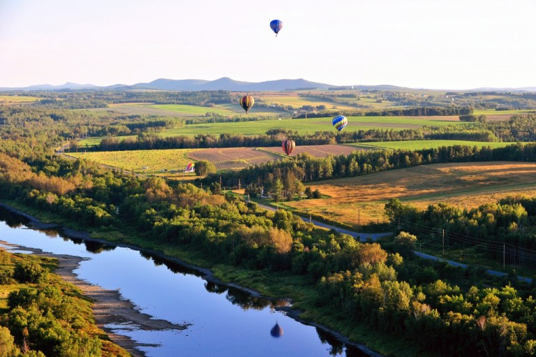 Hot air balloons over the Aroostook River in fall.