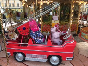 Lily-Belle and Matilda riding the carousel fire truck at the Helsinki Christmas Market in Senate Square