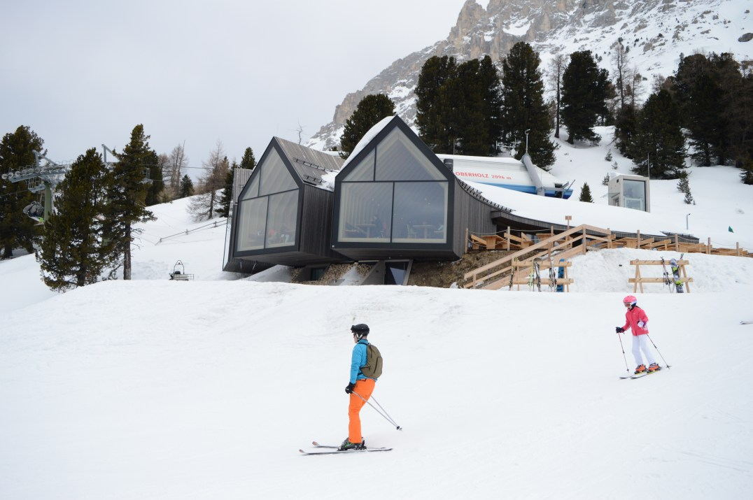 Skiers pass by the large windows of Oberholz Restaurant and Bar in Obereggen