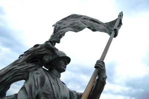 Bronze of Bersagliere soldier statue with flag in Trieste