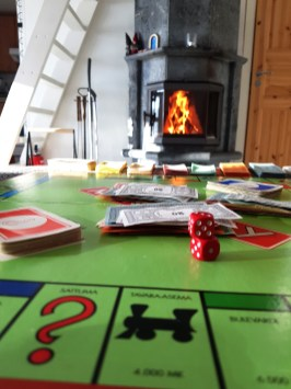 A game of Monopoly by the fire at A Cosy Cottage by the River in Rovaniemi