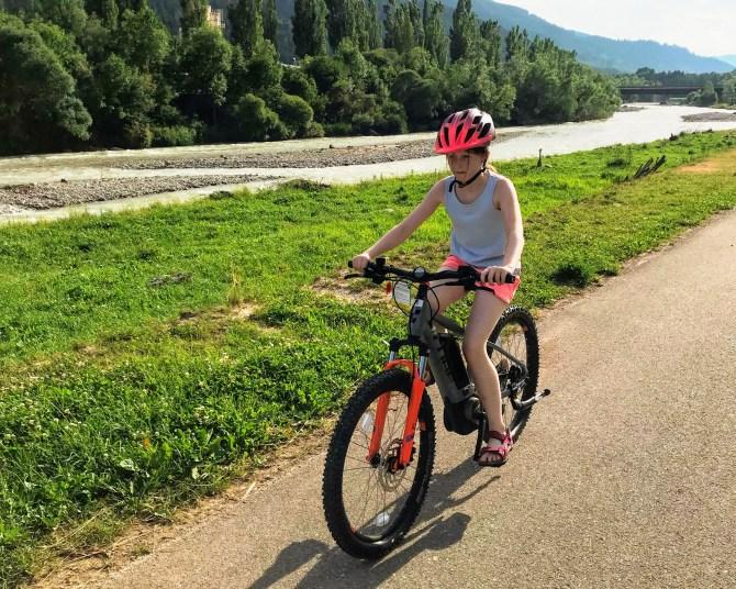 Lily-Belle e-biking beside the Torrente Avisio River in Ziano di Fiemme