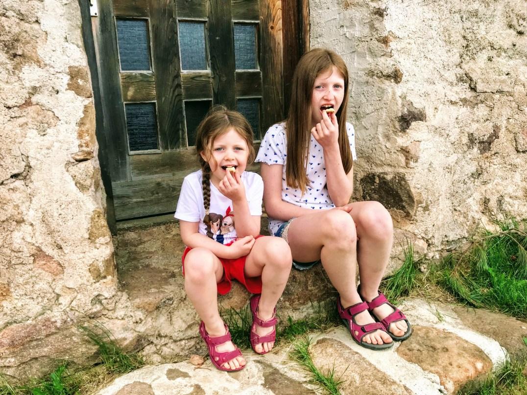 Matilda and Lily-Belle sampling fresh butter at Hut Malga Ora
