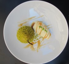 Dessert of poached pear with pistachio crust and ice cream with caramel sauce at Fosh Kitchen