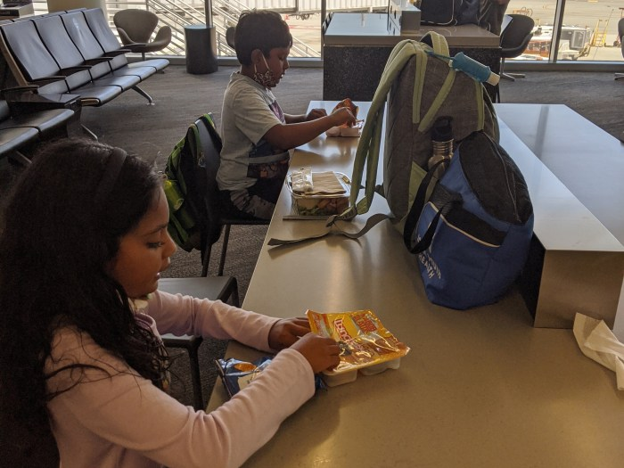 Two children eating at the airport