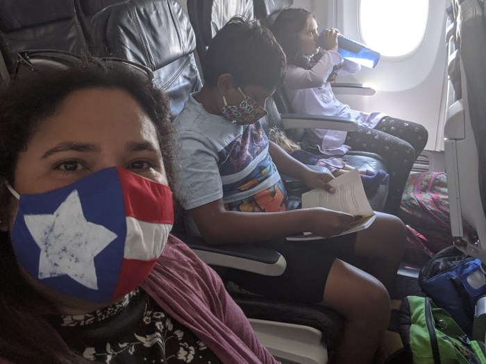 A mom and two children wearing masks and sitting on an airplane