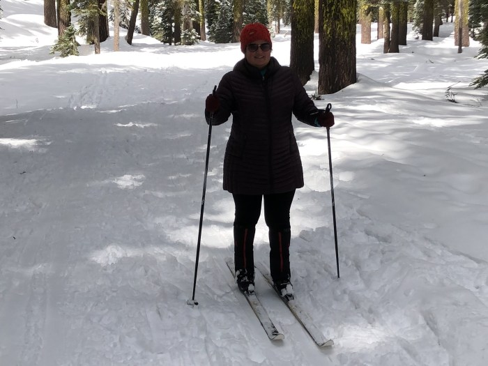 Woman on cross country skis with a long jacket, and orange hat