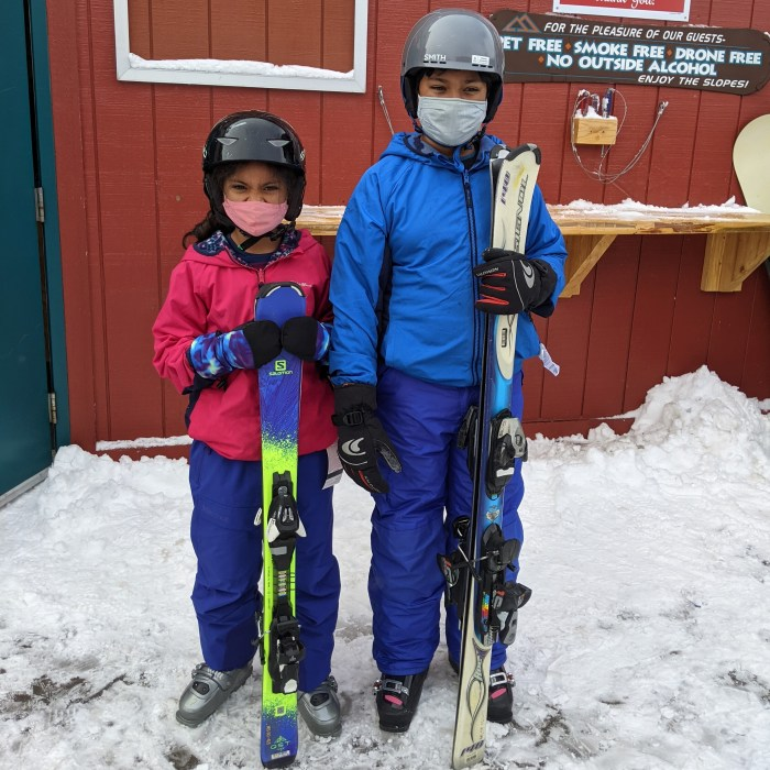 A boy and a girl in snow gear and helmets, with their skis