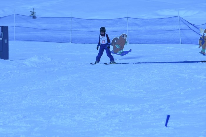A young girl on a training ski run, at the top of the hill.