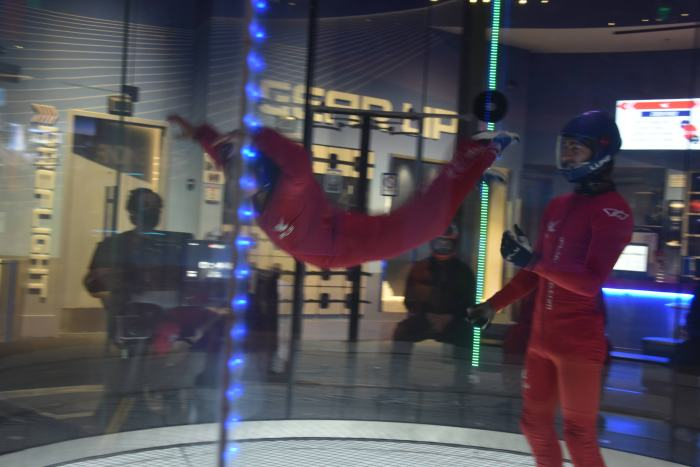 Young girl flying in a wind tunnel in a red flight suit
