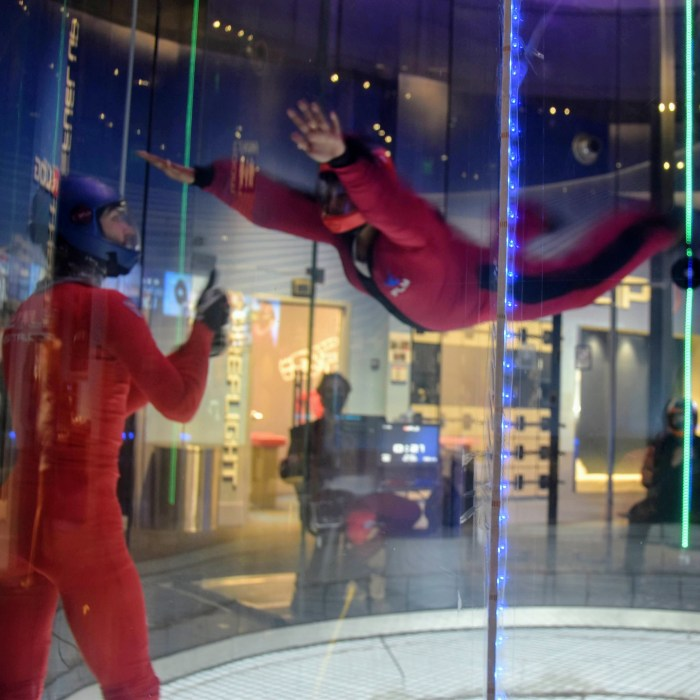 A young man floating solo in the indoor sky diving tube