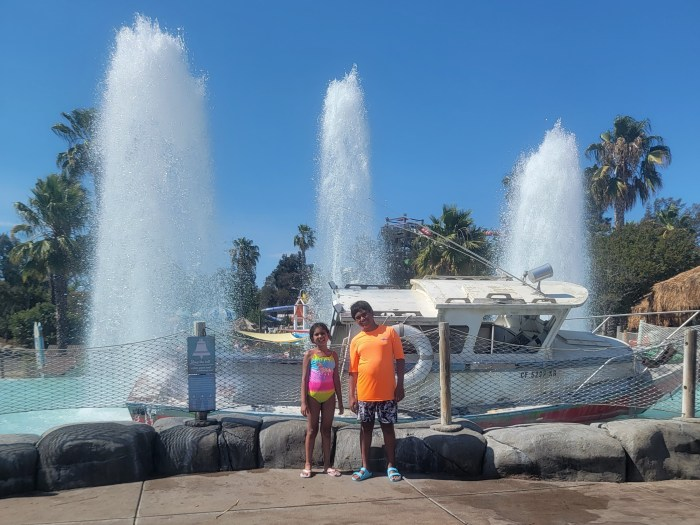Two children in front of a boat and water fountain