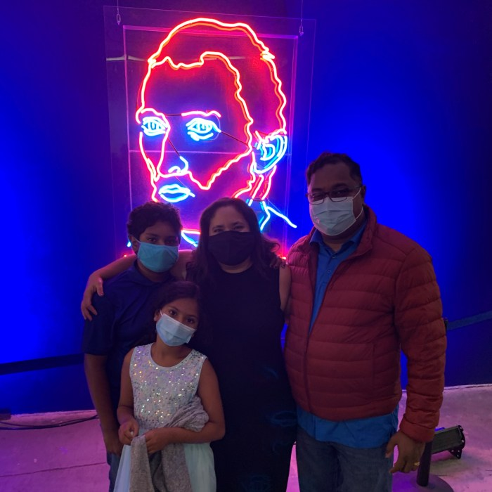A family of four in front of a neon version of a Van Gogh self portrait
