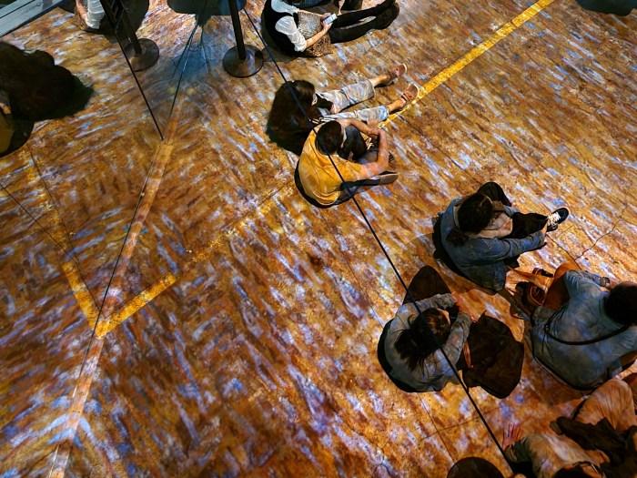 Patrons sitting on the floor of the Immersive Van Gogh exhibit