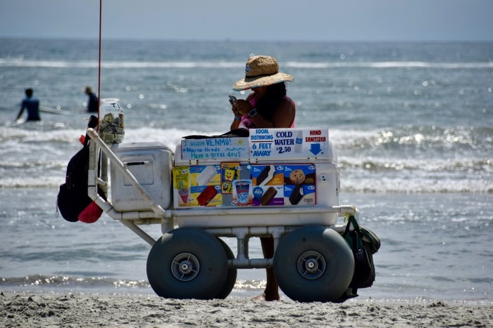 A wagon on the beach selling ice cream in front of the ocean