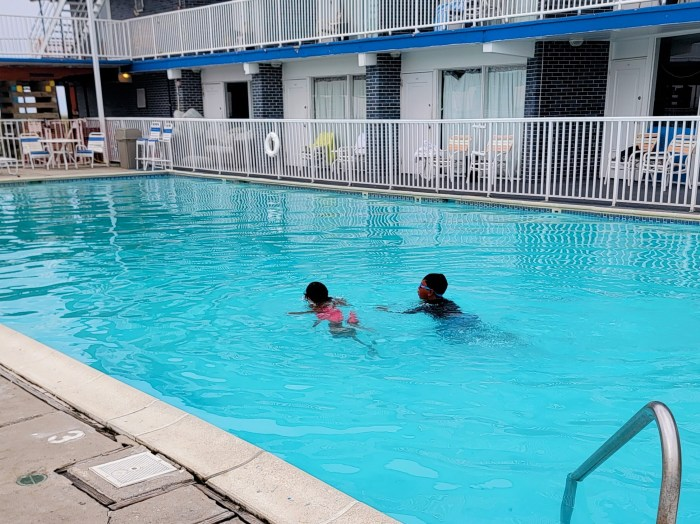 two children swimming in a large swimming pool
