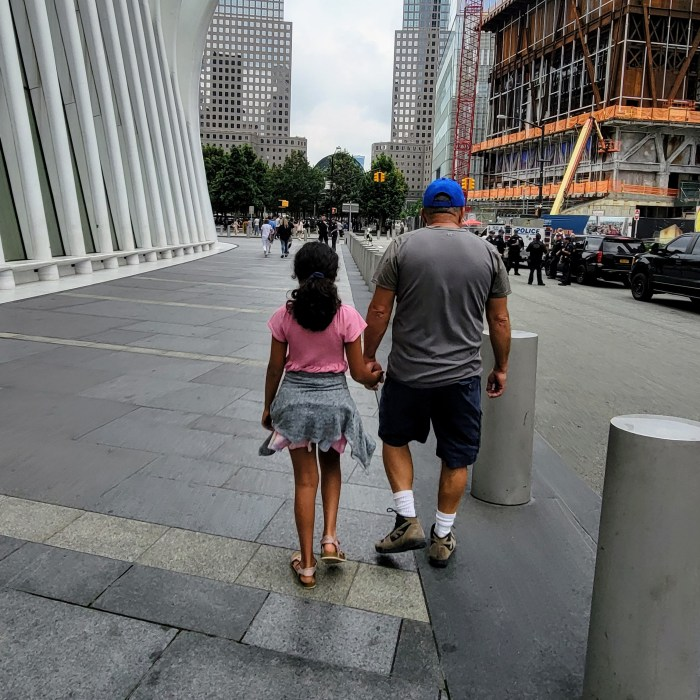 A grandfather and his granddaughter walking along side The Oculus