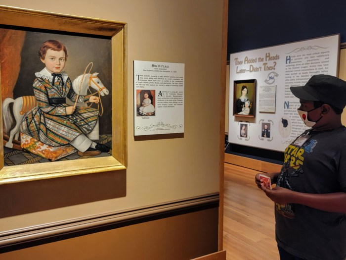 A young man looking at the painting of a little boy in a dress by a rocking horse