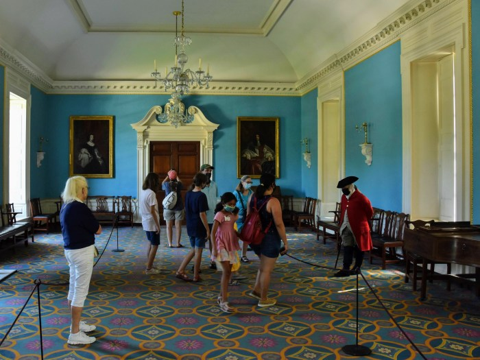 A blue ballroom with a blue and pink carpet, and harpsicord in an 18th century mansion